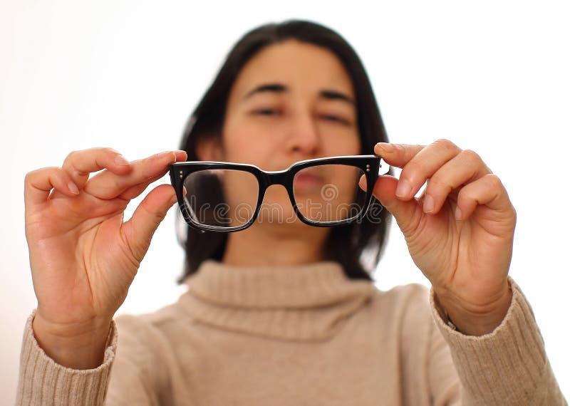 Mujer joven con los vidrios Desorden de Vision - problemas de la visión - visión borrosa fotos de archivo libres de regalías