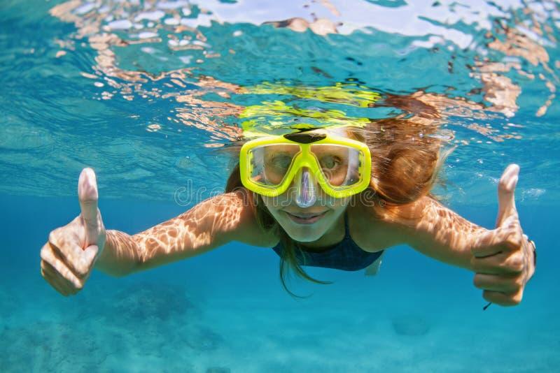 Mujer joven con máscara de buceo bucea bajo el agua con peces tropicales imagen de archivo