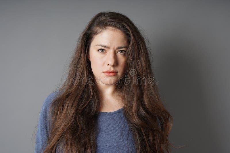 Mujer joven con mirada seria en su cara fotos de archivo