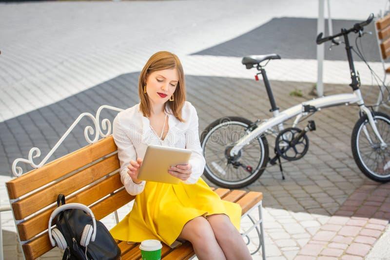 Mujer joven con PC de la tableta en el parque imagenes de archivo