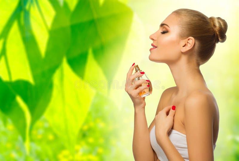 Mujer joven con perfume en fondo floral foto de archivo