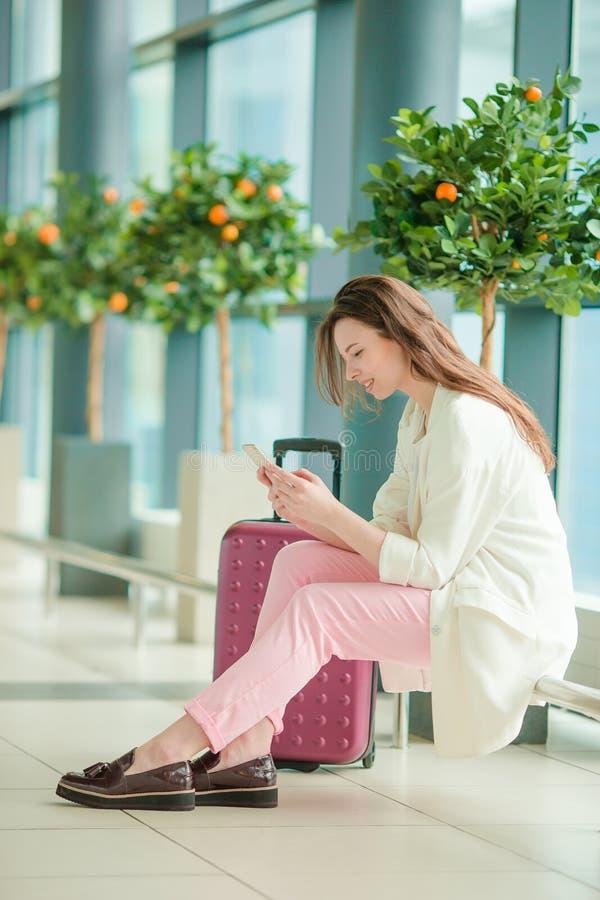Mujer joven con smartphone en vuelo que espera del aeropuerto internacional para fotos de archivo