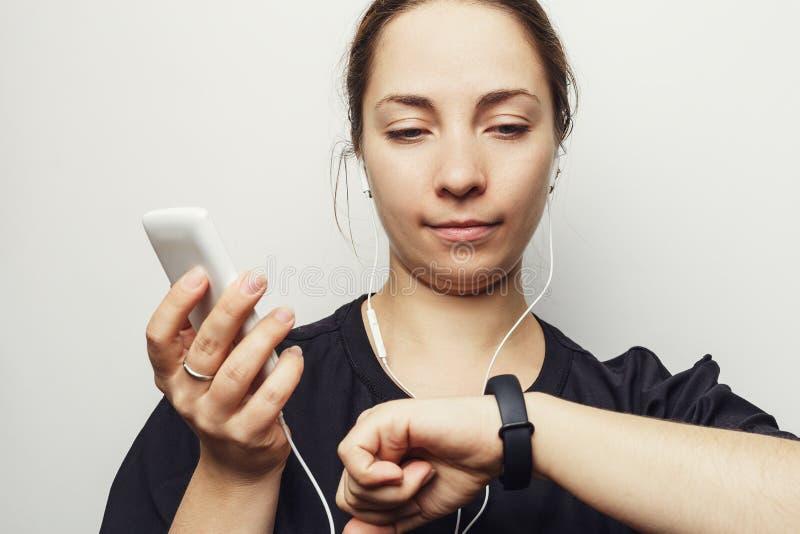 Mujer joven con smartphone y auriculares que miran la pulsera de la aptitud o al perseguidor elegante de la actividad con el podó fotos de archivo libres de regalías