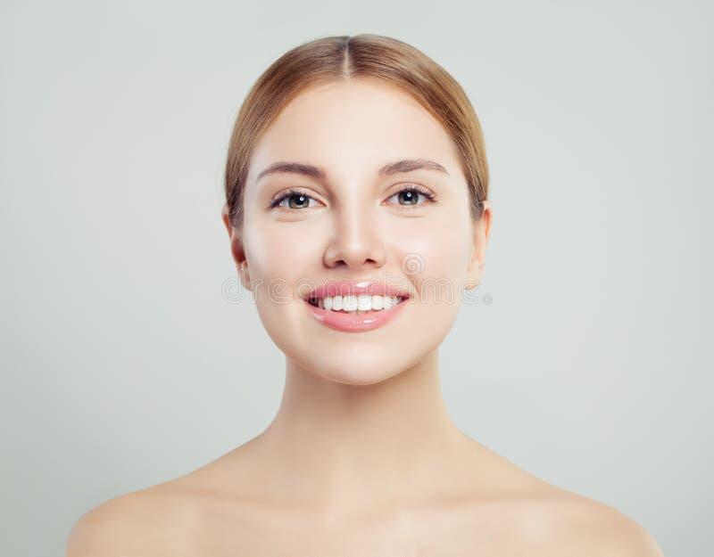 Mujer joven con sonrisa perfecta Muchacha sonriente con la piel clara en el fondo blanco Tratamiento y skincare faciales fotos de archivo