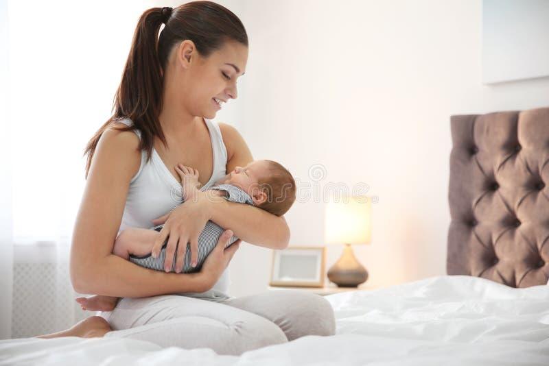 Mujer joven con su bebé recién nacido en dormitorio fotos de archivo