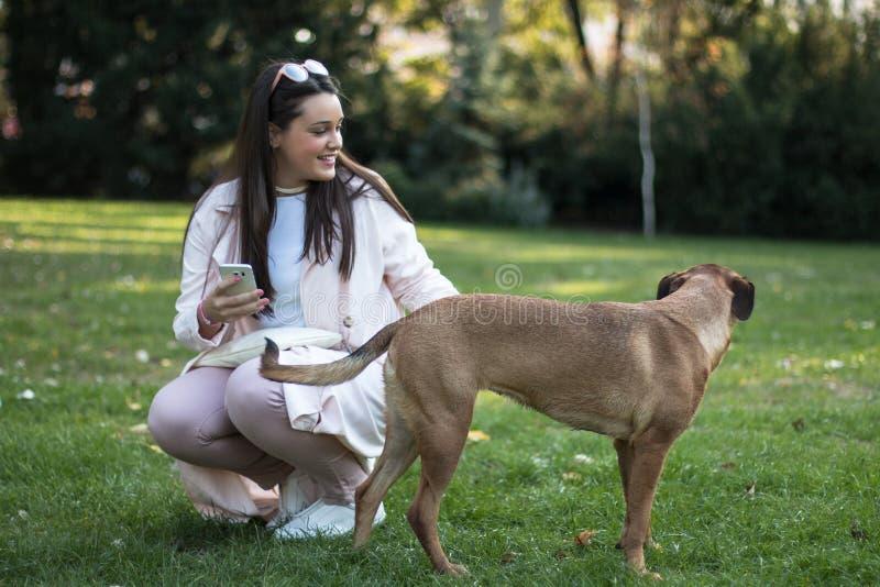 Mujer joven con su perro casero en el parque fotografía de archivo