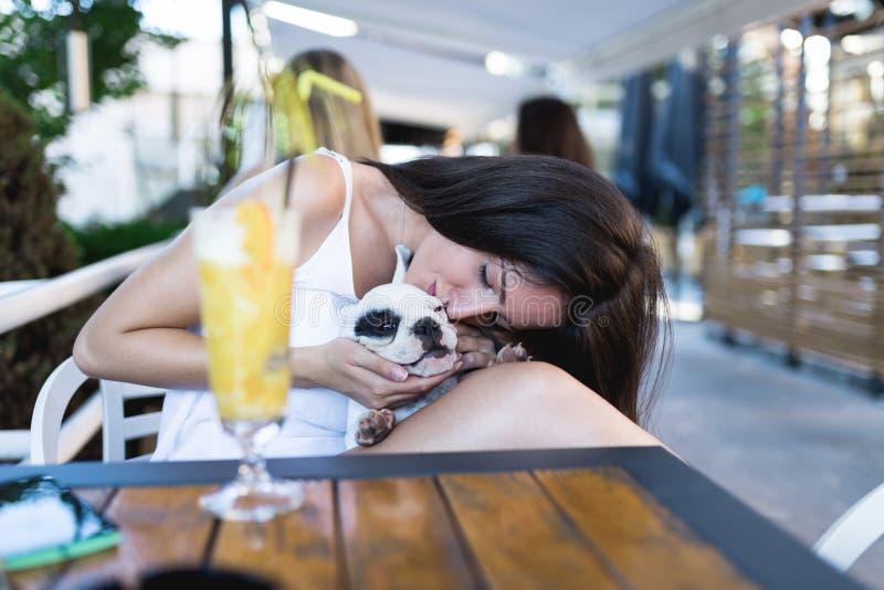 Mujer joven con su perro en barra del café foto de archivo