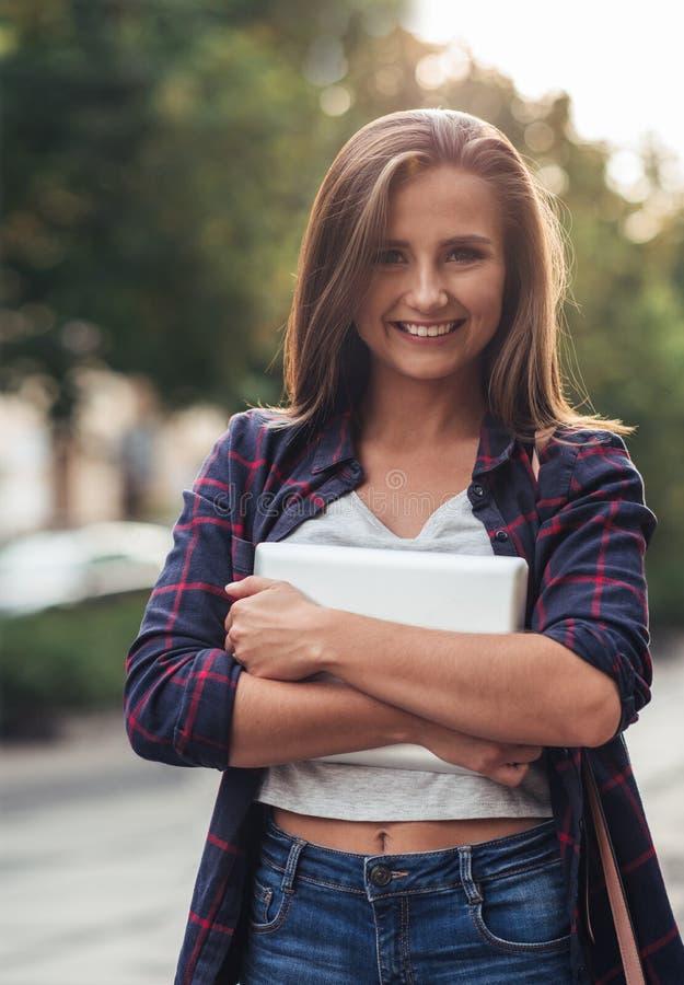Mujer joven con su tableta digital en la ciudad imagen de archivo