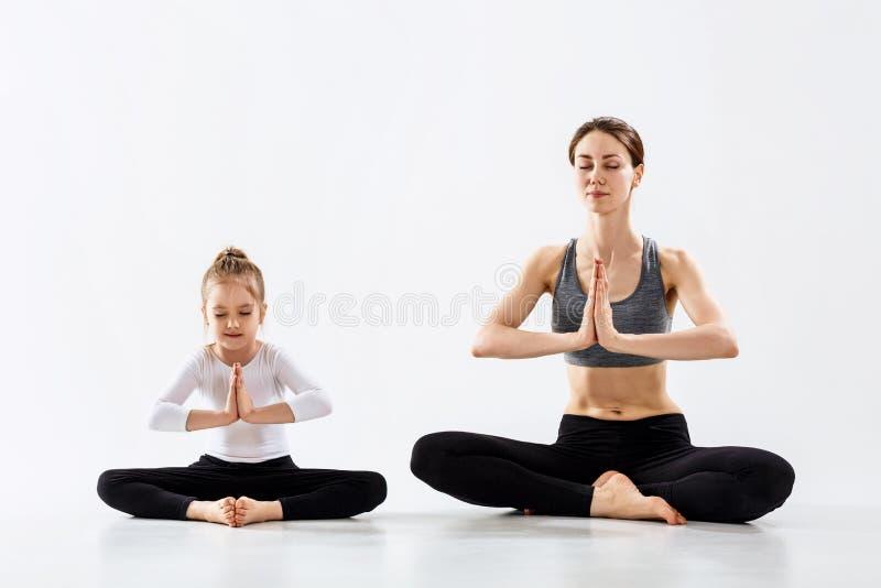 Mujer joven con su yoga practicante de la pequeña hija junto fotografía de archivo libre de regalías