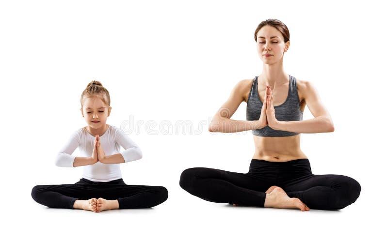 Mujer joven con su yoga practicante de la pequeña hija junto imagenes de archivo