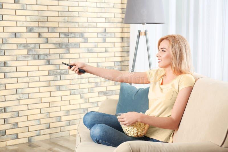 Mujer joven con teledirigido y cuenco de palomitas que ve la TV foto de archivo libre de regalías