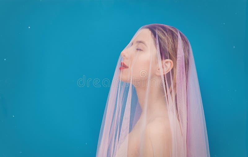 Mujer joven con Tulle rosada en fondo azul imagenes de archivo