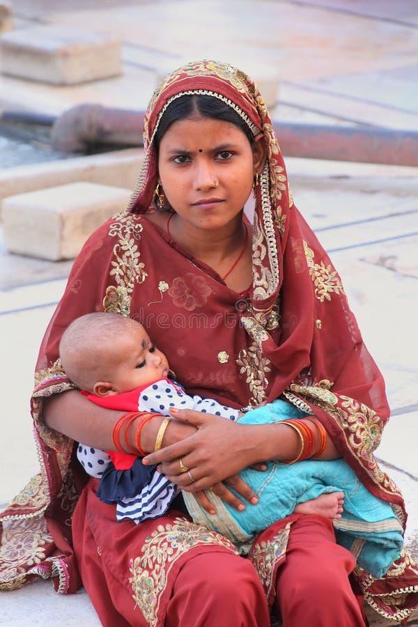 Mujer joven con un bebé que se sienta en Jama Masjid, Delhi, la India fotos de archivo libres de regalías