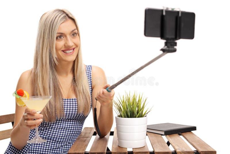 Mujer joven con un cóctel que se sienta en una tabla y que toma a un uno mismo fotografía de archivo