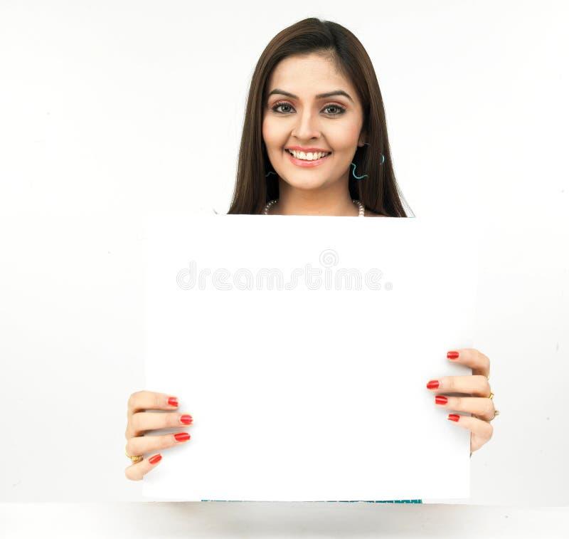 Mujer joven con un cartel en blanco imagenes de archivo