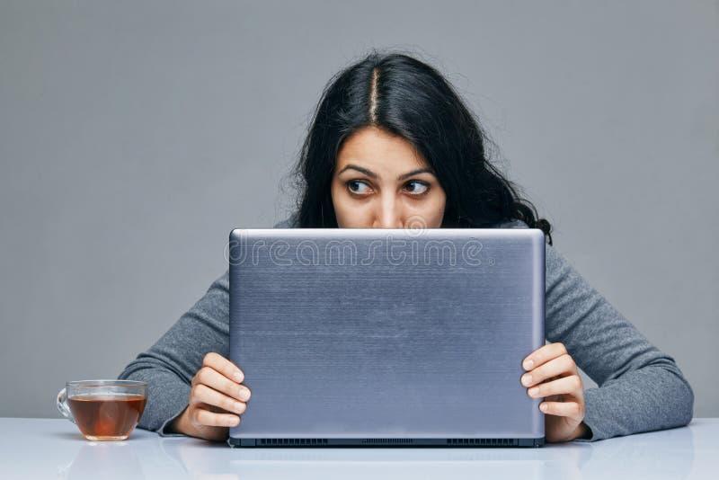 Mujer joven con un ordenador Ella no conoce qué hacer después fotografía de archivo libre de regalías