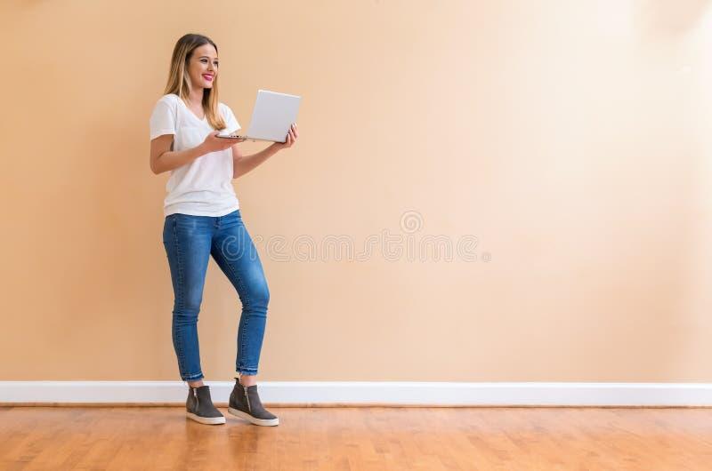 Mujer joven con un ordenador portátil imagenes de archivo