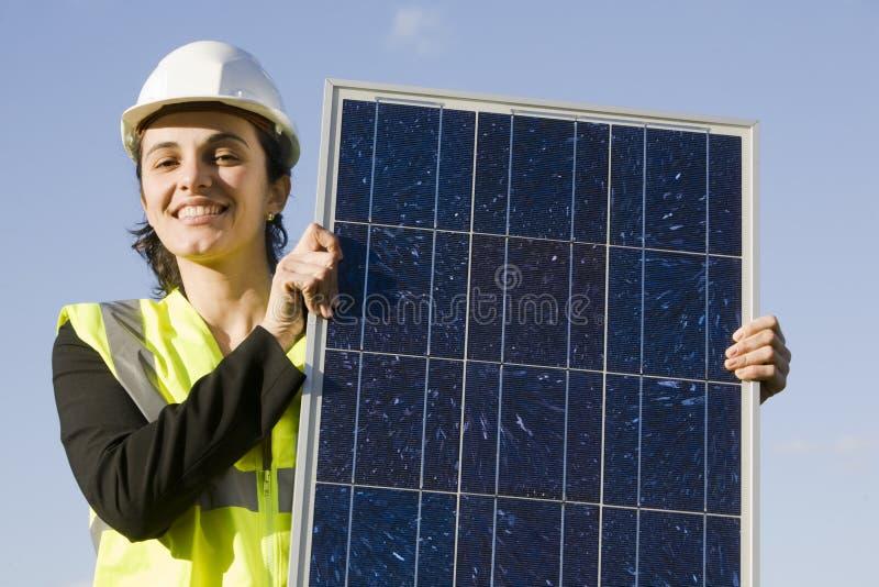 Mujer joven con un panel solar fotos de archivo