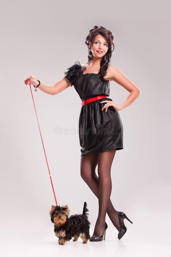 Mujer joven con un pequeño perro imágenes de archivo libres de regalías