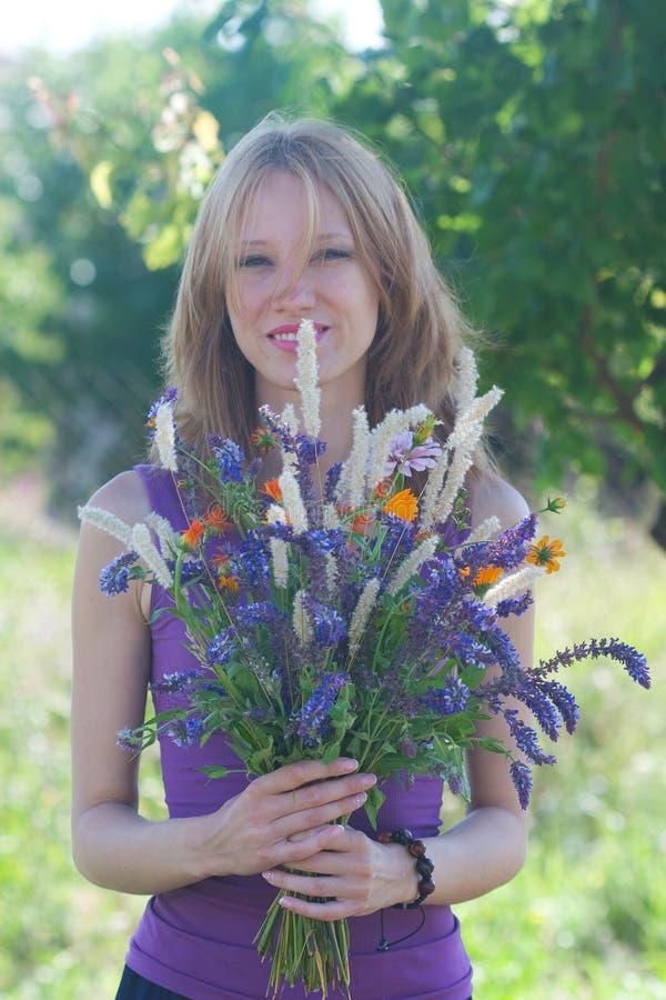 Mujer joven con un ramo de flores salvajes foto de archivo