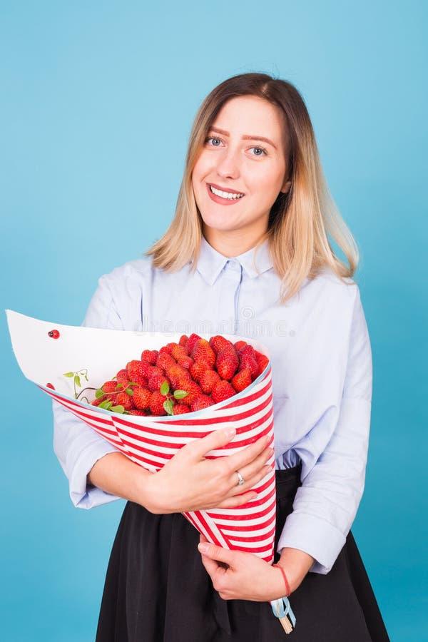 Mujer joven con un ramo de fresa fotos de archivo libres de regalías