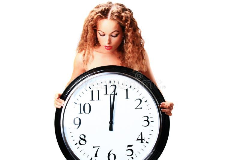 Mujer joven con un reloj de pared fotos de archivo libres de regalías