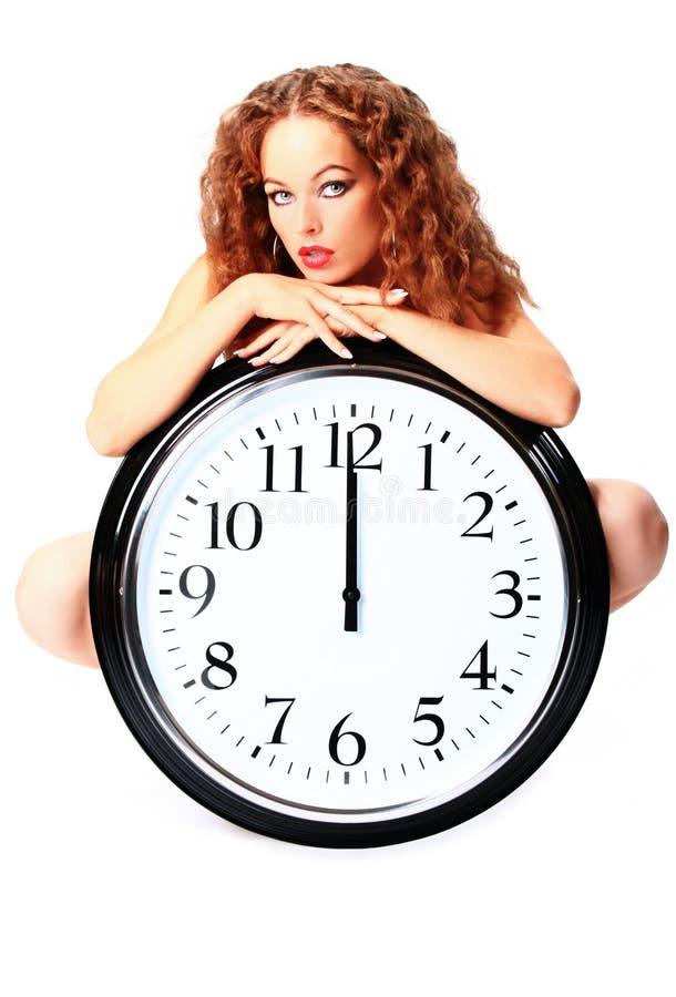 Mujer joven con un reloj de pared imagenes de archivo