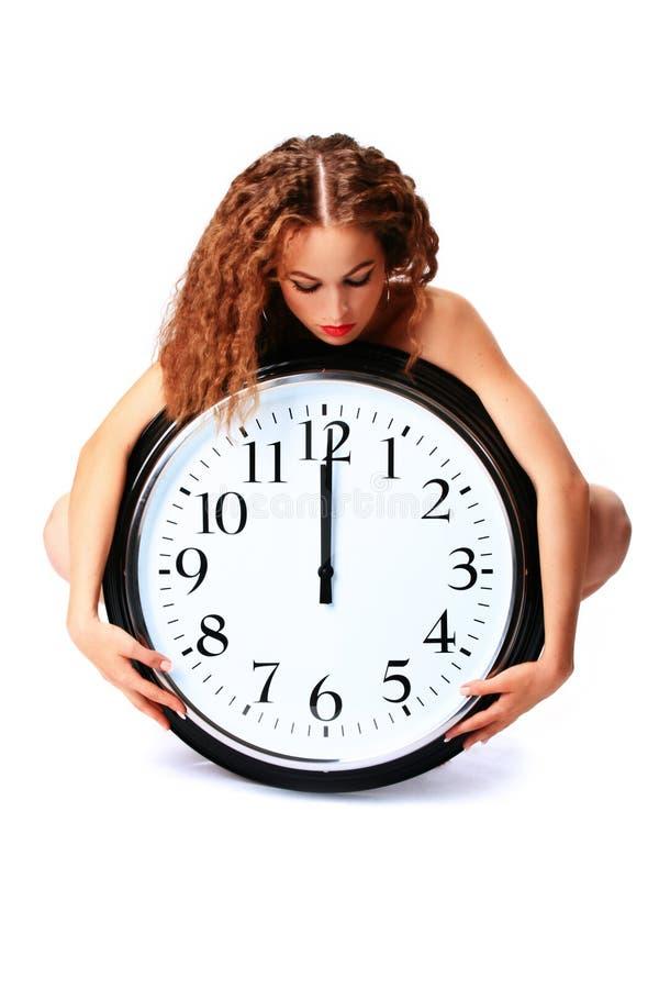 Mujer joven con un reloj de pared imagen de archivo
