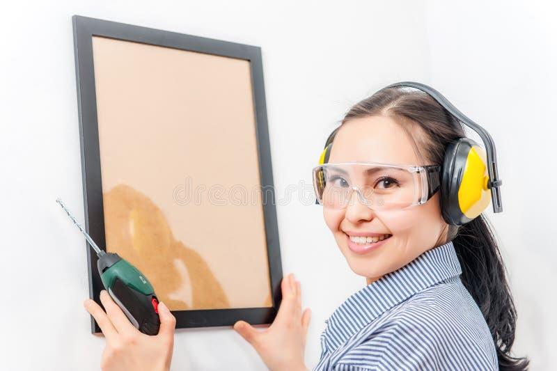 Mujer joven con un taladro imágenes de archivo libres de regalías