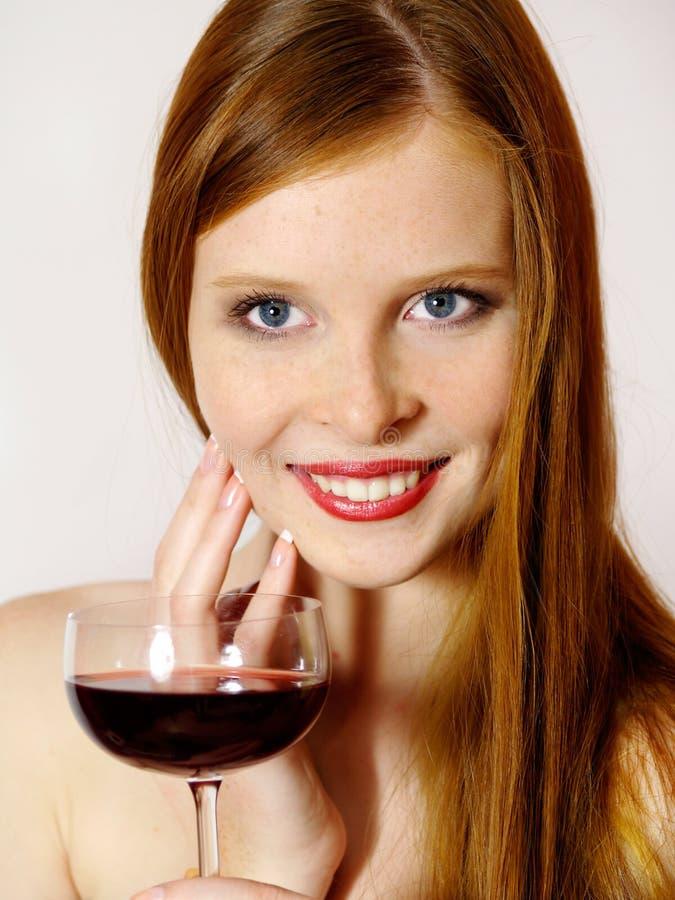 Mujer joven con un vidrio de vino rojo fotografía de archivo