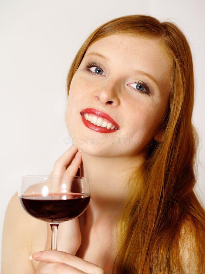 Mujer joven con un vidrio de vino rojo imagen de archivo