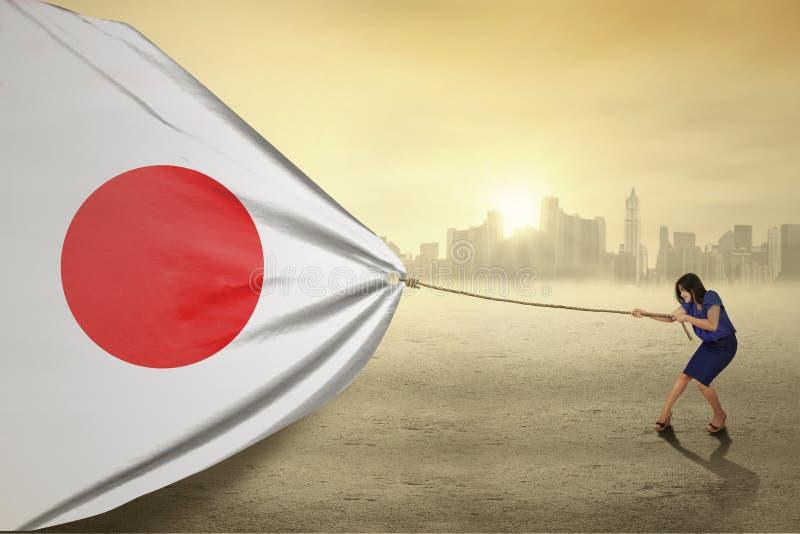 Mujer joven con una bandera de Japón foto de archivo