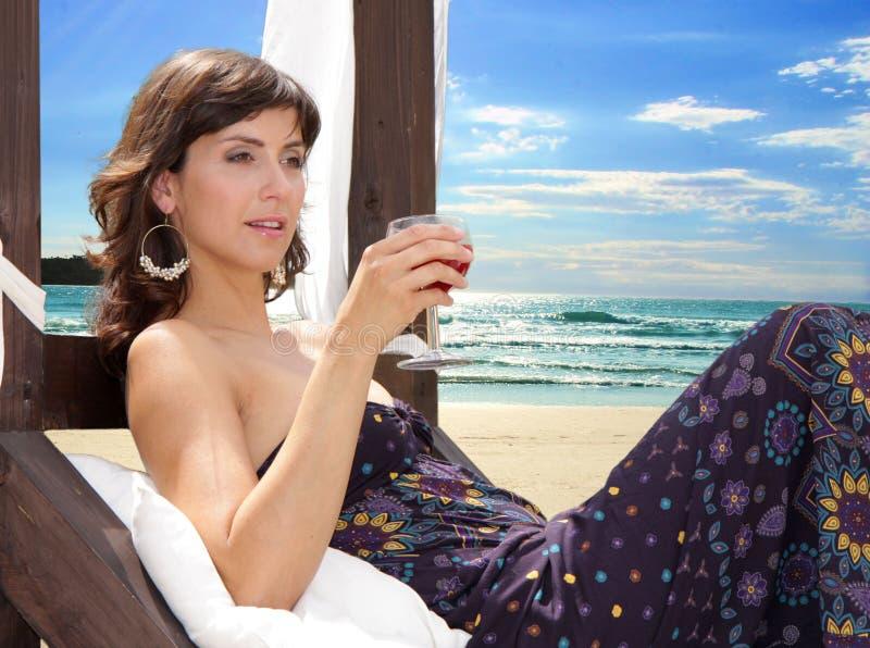 Mujer joven con una bebida en la playa imagen de archivo libre de regalías
