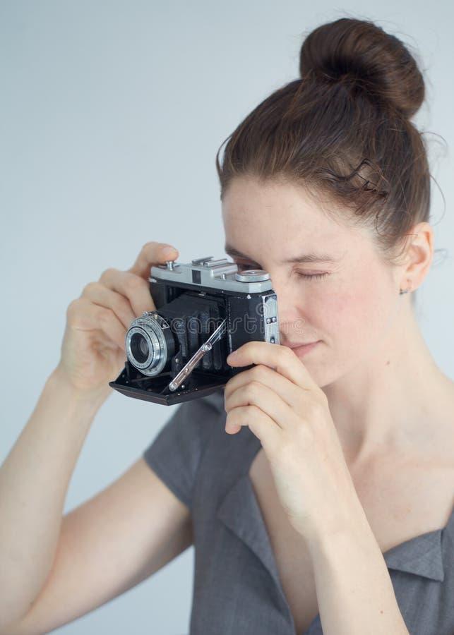 Mujer joven con una cámara de zeiss fotos de archivo libres de regalías