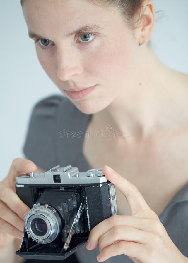 Mujer joven con una cámara de zeiss foto de archivo