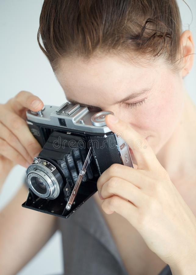 Mujer joven con una cámara de zeiss imagen de archivo
