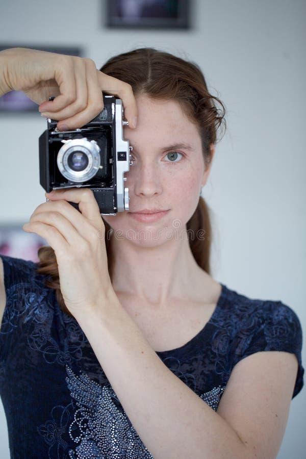 Mujer joven con una cámara de zeiss fotografía de archivo