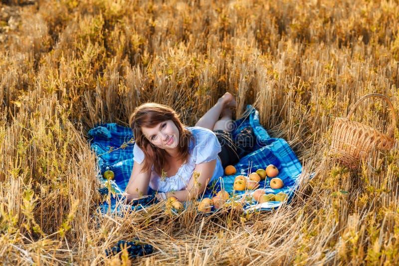 Mujer joven con una cesta de fruta imagen de archivo