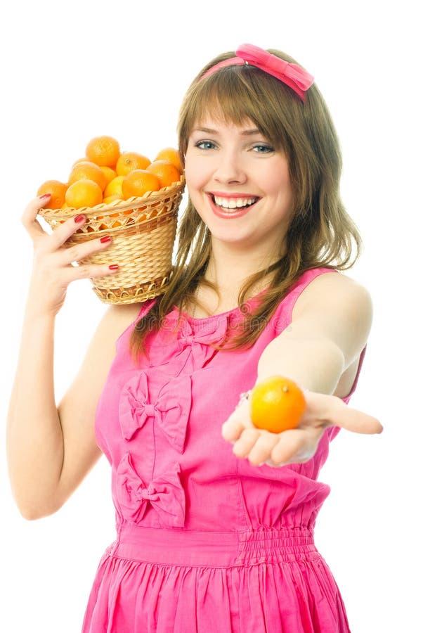 Mujer joven con una cesta llena de mandarinas foto de archivo