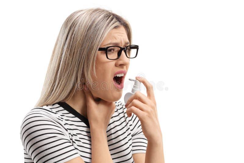 Mujer joven con una garganta dolorida usando un espray de la boca fotos de archivo