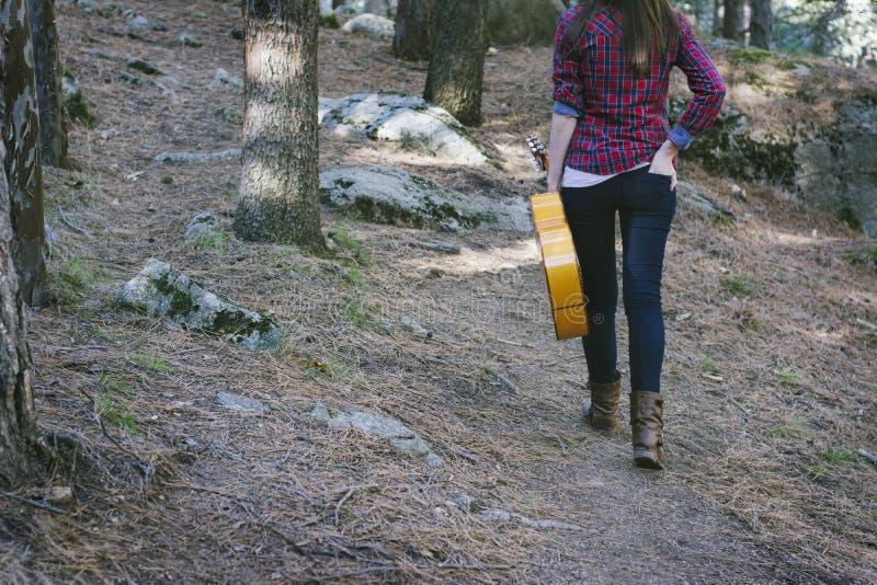Mujer joven con una guitarra a disposición, caminando detrás con la delantera fotos de archivo