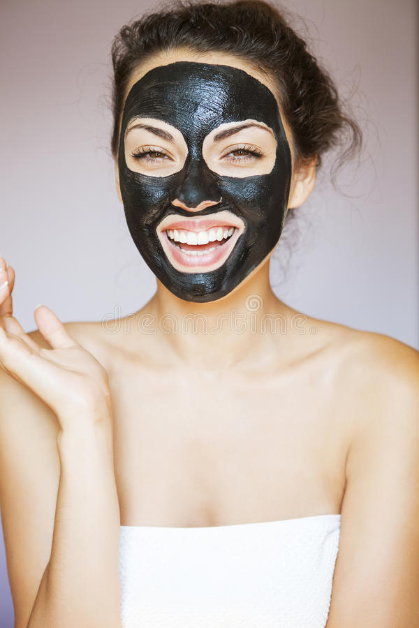 Mujer joven con una máscara para la cara del negro terapéutico MU imagen de archivo libre de regalías