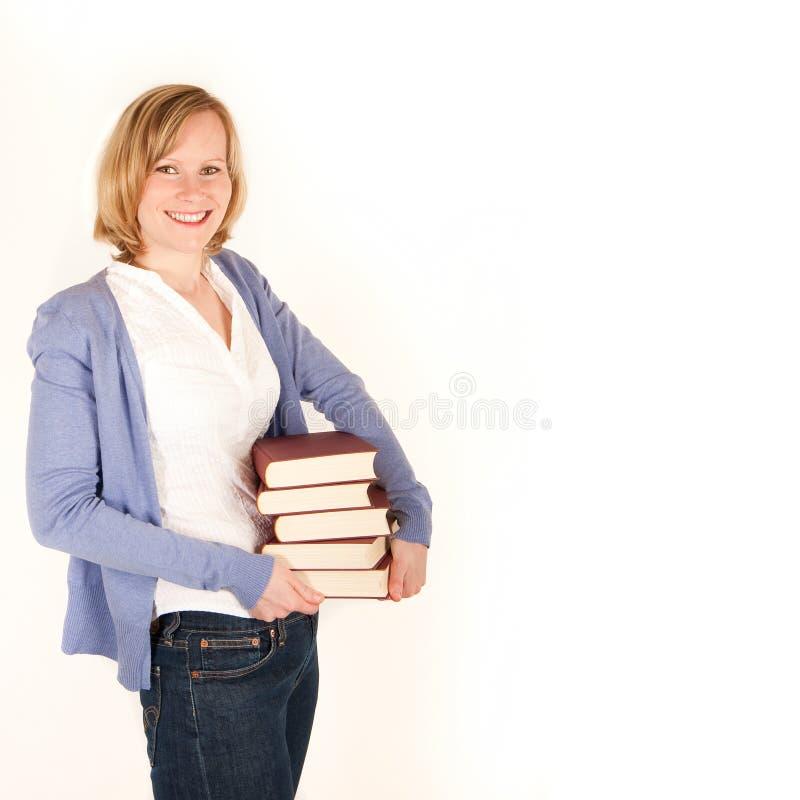 Mujer joven con una pila de libros imagenes de archivo