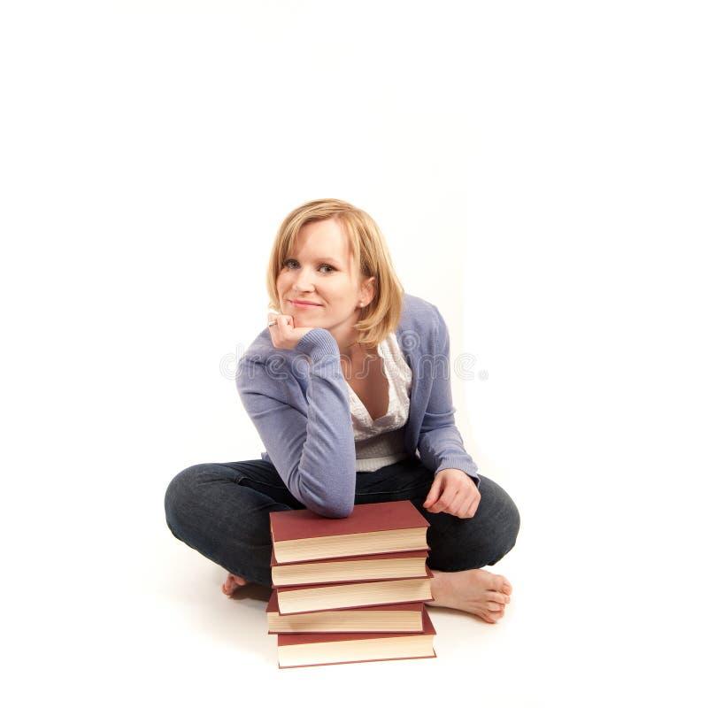 Mujer joven con una pila de libros imágenes de archivo libres de regalías