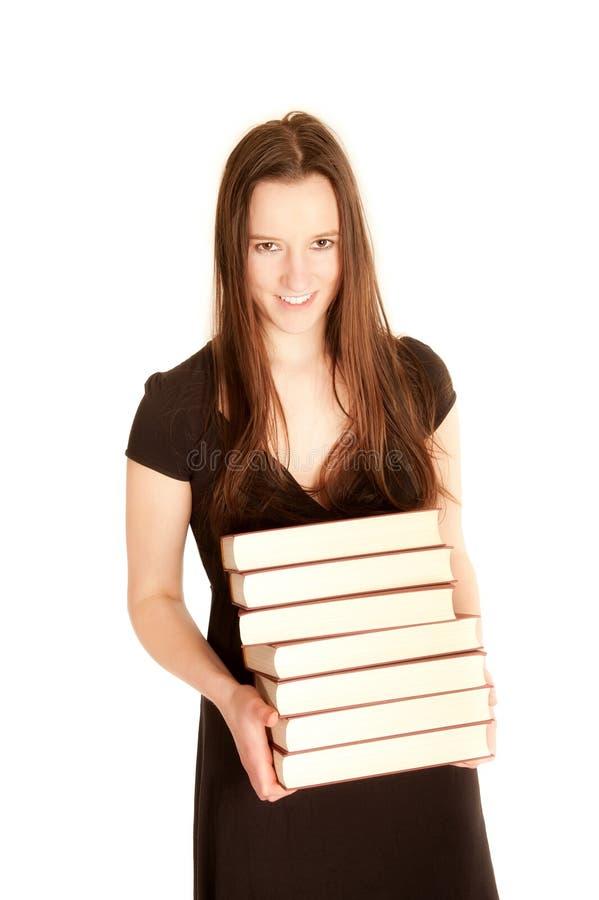 Mujer joven con una pila de libros fotografía de archivo
