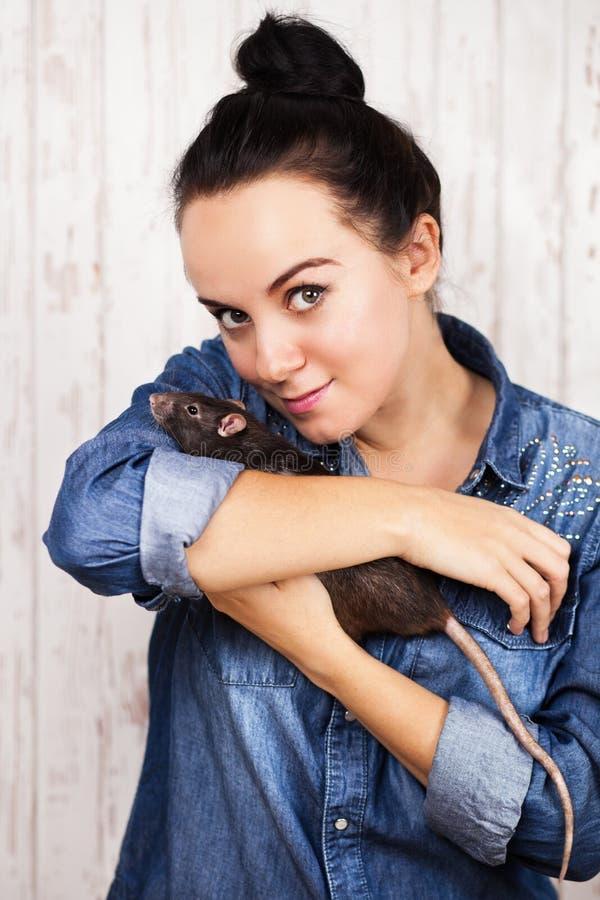 Mujer joven con una rata del animal doméstico foto de archivo