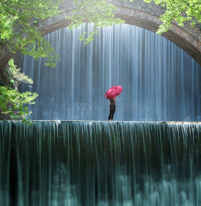 Mujer joven con una situación roja y miradas del paraguas en la cascada imágenes de archivo libres de regalías