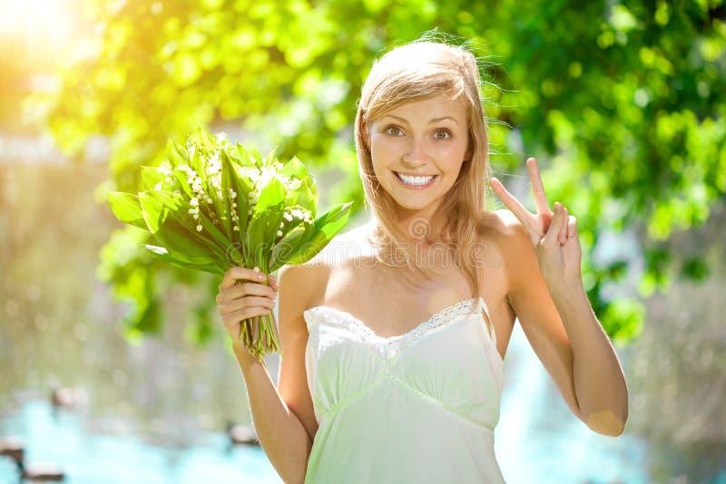 Mujer joven con una sonrisa hermosa con los dientes sanos con el flowe imagenes de archivo