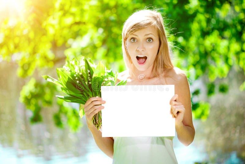 Mujer joven con una sonrisa hermosa con los dientes sanos con el flowe fotos de archivo