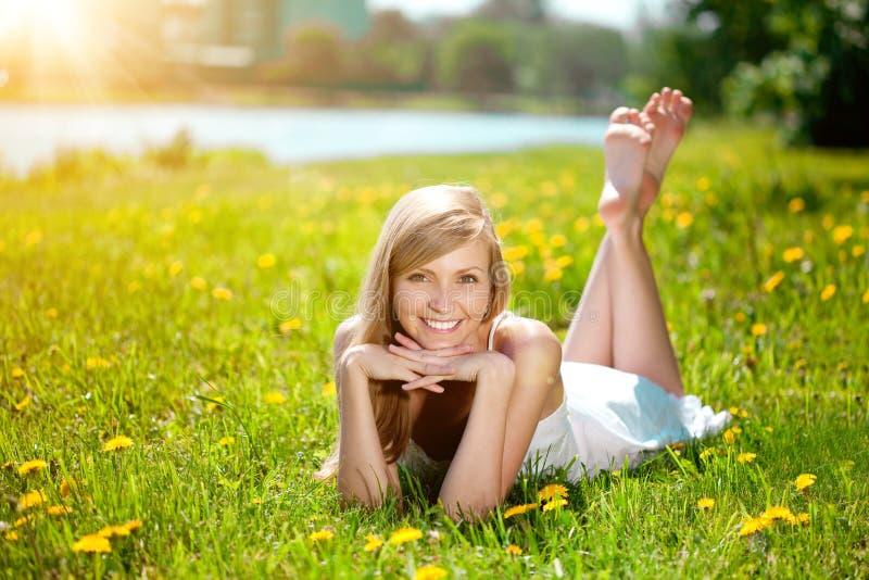 Mujer joven con una sonrisa hermosa con los dientes sanos con el flowe imágenes de archivo libres de regalías